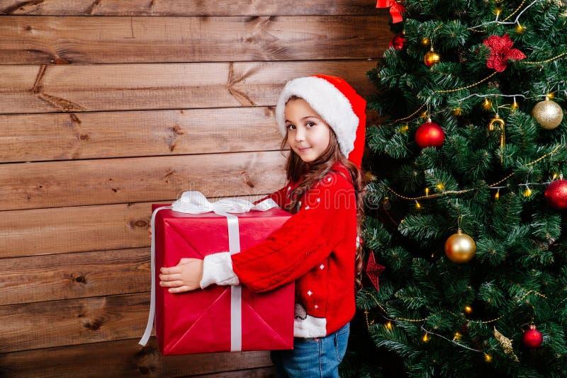 Feliz Navidad y día de fiesta feliz Muchacha linda del pequeño niño con la actual caja de regalo roja grande cerca del árbol inte foto de archivo