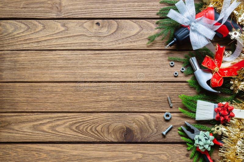Feliz Navidad y herramientas prácticas de la construcción de la Feliz Año Nuevo detrás imagen de archivo