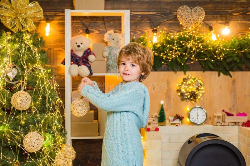 Feliz Navidad y Feliz A?o Nuevo. Niño lindo decorando el árbol de Navidad con baudible - tradición de Año Nuevo. decorating fotografía de archivo libre de regalías