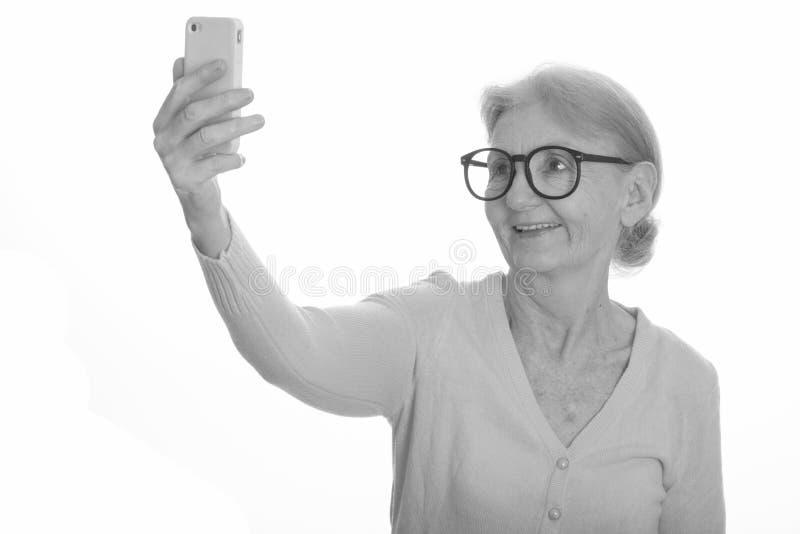 Explicando o emissão de chakra - Página 3 Feliz-nerd-sorrir-e-receber-selfie-com-o-telefone-celular-retrato-studio-de-mulher-idosa-baleada-preto-branco-160301248