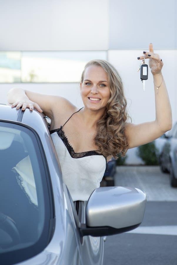 Feliz nuevo dueño de auto con llave y una sonrisa foto de archivo