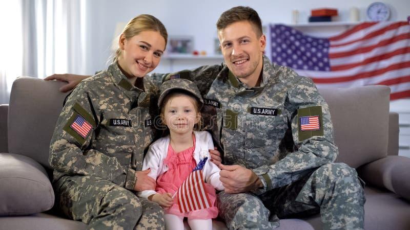 Feliz pareja de soldados americanos e hija con bandera de Estados Unidos sonriendo a cámara imágenes de archivo libres de regalías