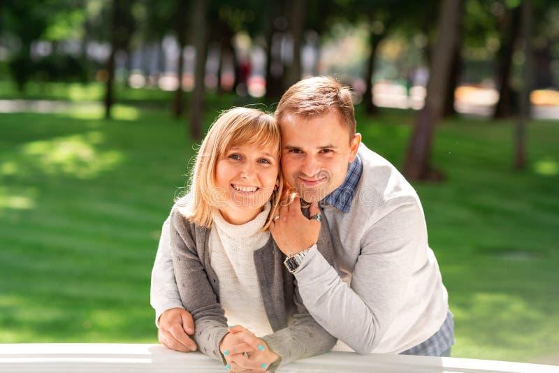 Feliz pareja joven abrazándose y riendo juntos en el parque fotografía de archivo libre de regalías