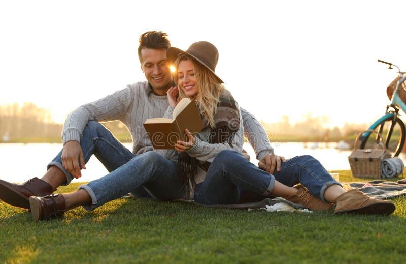 Feliz pareja joven leyendo un libro mientras toma picnic fotografía de archivo