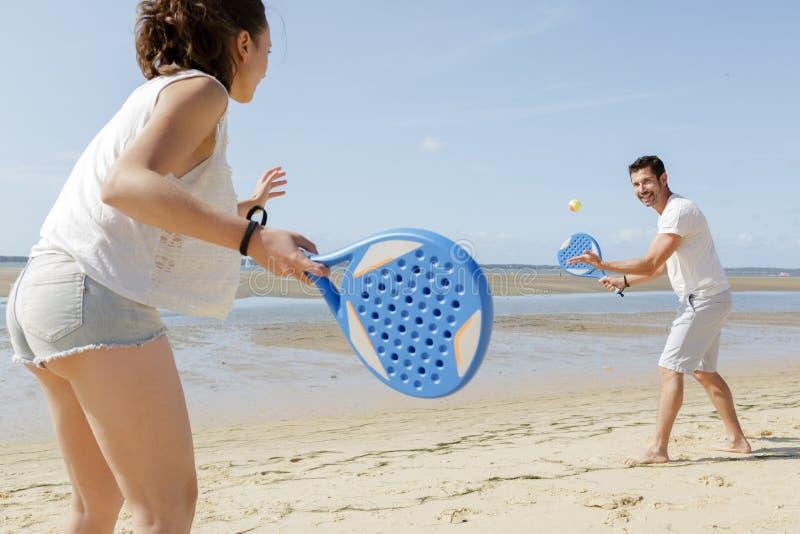 Feliz pareja jugando al tenis en la playa fotos de archivo libres de regalías