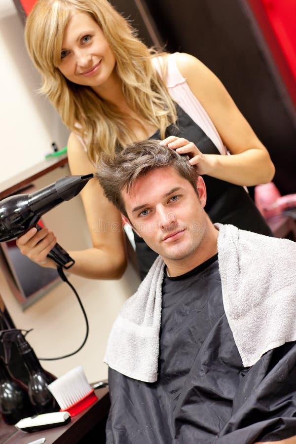 Feliz pelo de su cliente del peluquero sequedad imagen de archivo