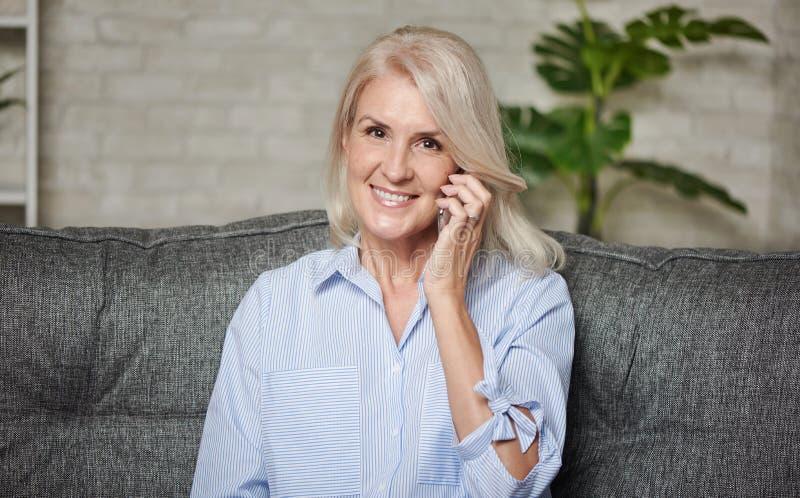 Feliz que una mujer de 50 años hable por teléfono fotos de archivo