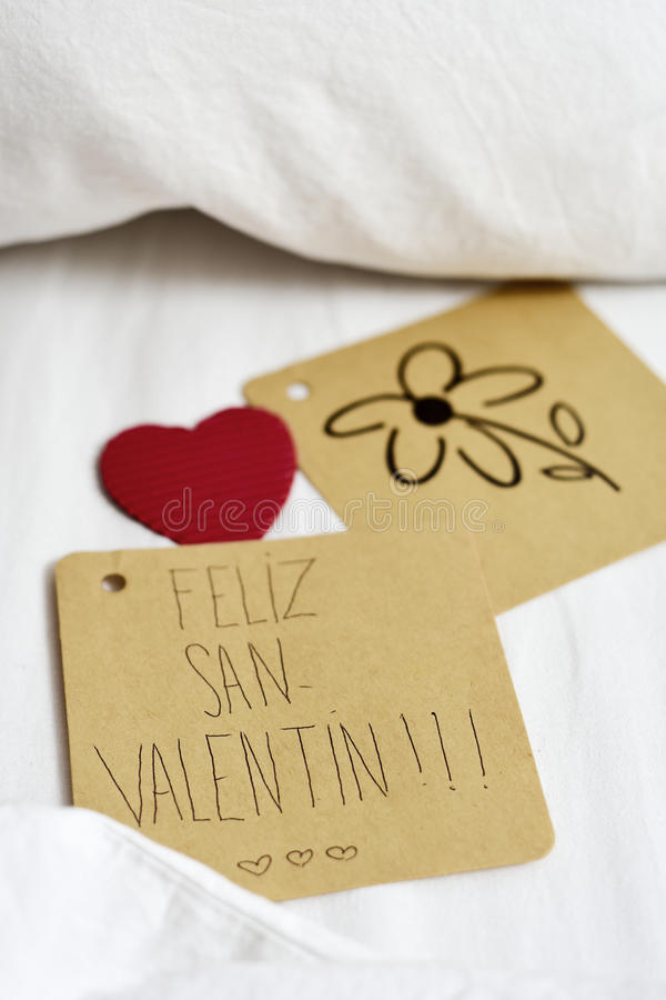 Feliz san valentin, happy valentines day in spanish. Closeup of a brown paper note with the text feliz san valentin, happy valentines day written in Spanish and royalty free stock photos