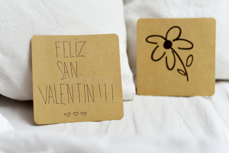 Feliz san valentin, happy valentines day in Spanish. Closeup of a brown paper note with the text feliz san valentin, happy valentines day written in Spanish and stock photos