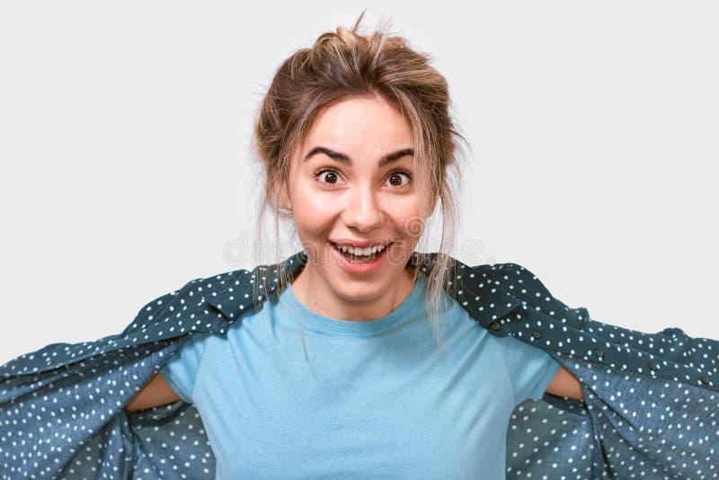 Feliz surpreendeu a mulher bonita nova no t-shirt azul, sorrindo amplamente, olhando alegre e excitado à câmera imagem de stock royalty free