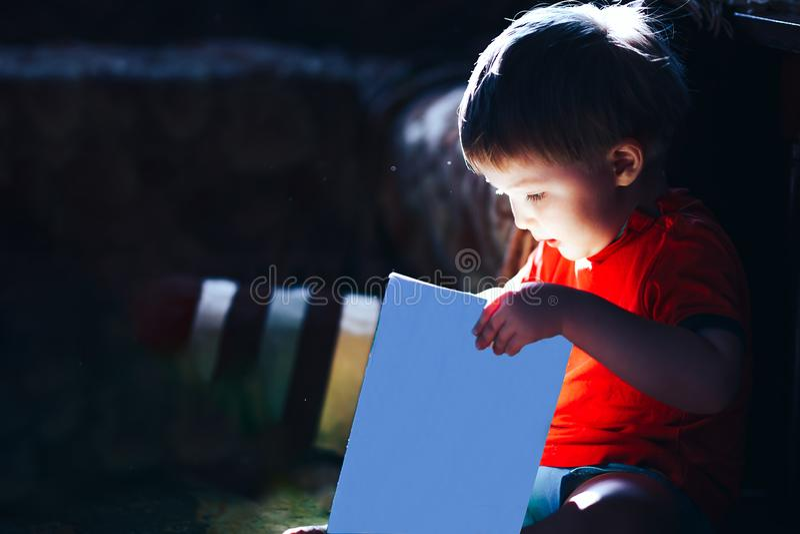 Feliz surpreendido tr?s anos de conto de fadas m?gico velho do livro de leitura do menino no fundo escuro, luz vem do livro, livr foto de stock