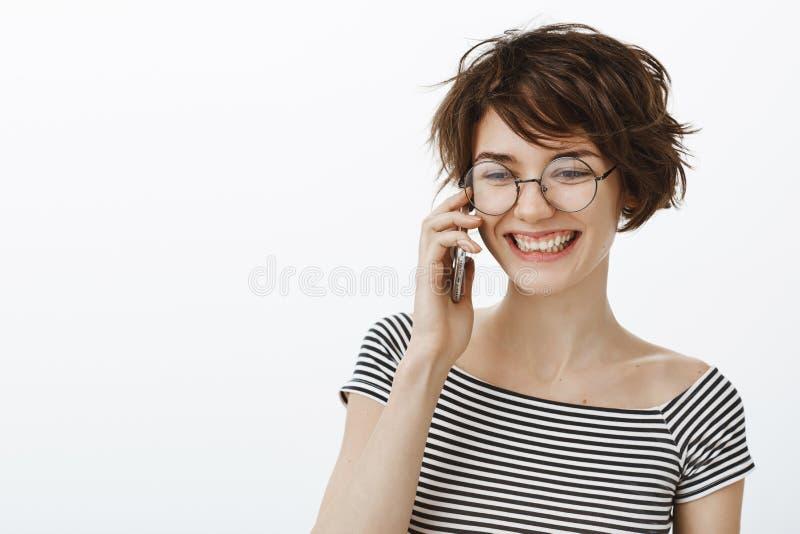 Feliz usted llamada Retrato del amigo femenino positivo feliz en vidrios redondos y camiseta rayada, mirando a un lado con alegre imagen de archivo libre de regalías