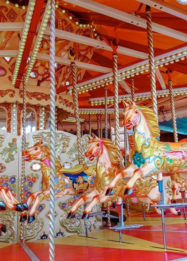 Feliz va la ronda en el parque de atracciones, caballos fotos de archivo