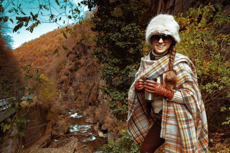 Feliz viajante mujer con barro termo de acero inoxidable fotos de archivo libres de regalías