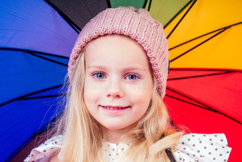 Feliz y divertida rubia con los ojos azules, niño con un paraguas color arco iris en el parque de otoño. Niña jugando fotografía de archivo libre de regalías
