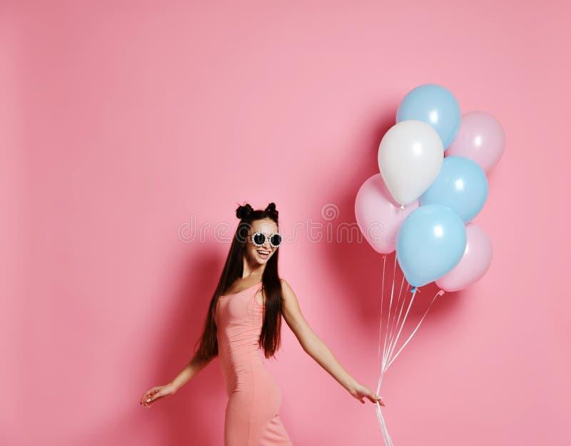 Feliz y mujer que presentan con rosa y los globos azules en el fondo rosado, tiro del estudio foto de archivo libre de regalías