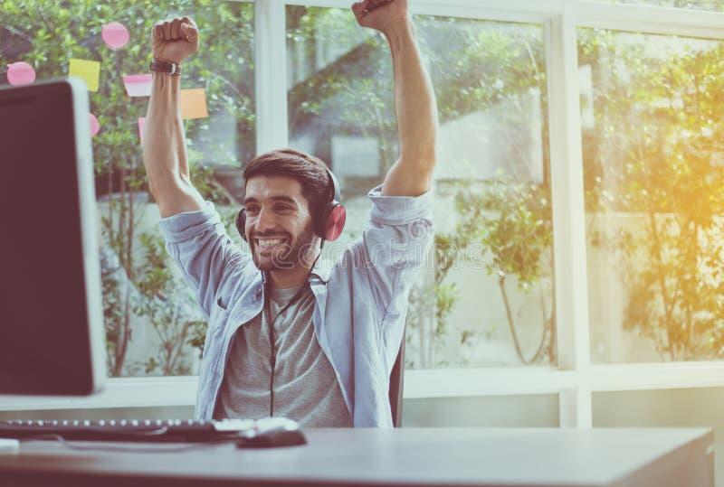 Feliz y sonriendo, relaje el tiempo, rais acertados de las manos de los hombres para arriba con el juego del ganador en línea fotos de archivo libres de regalías