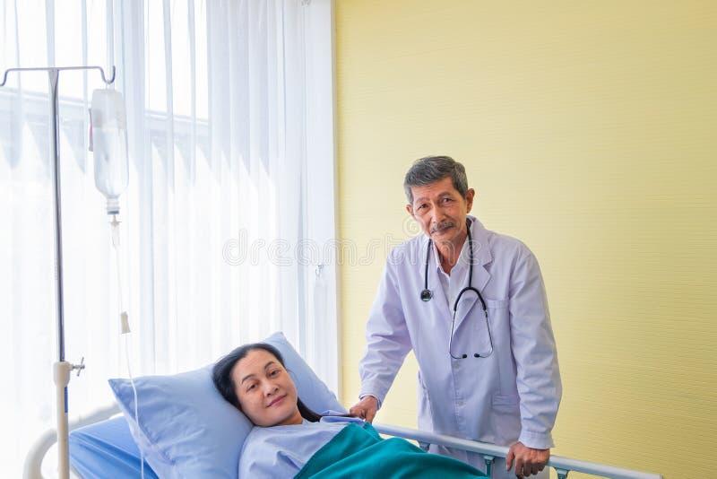 Feliz y sonrisa, doctor de sexo masculino asiático mayor que visita al paciente femenino de mediana edad en sala en hospital del  foto de archivo libre de regalías