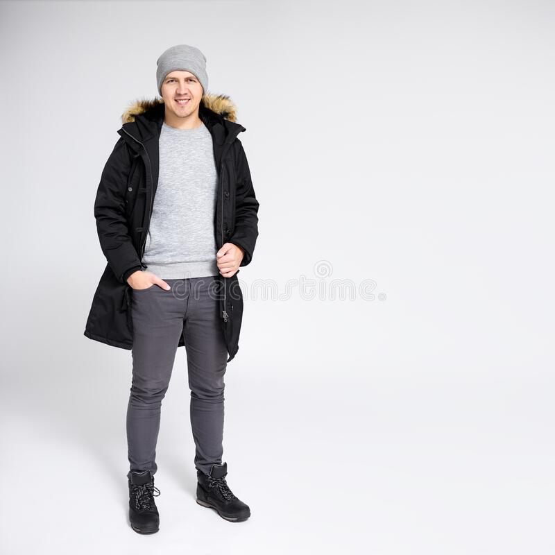 Fell length portrait of young handsome man in warm winter clothes over gray background with copy space stock photo