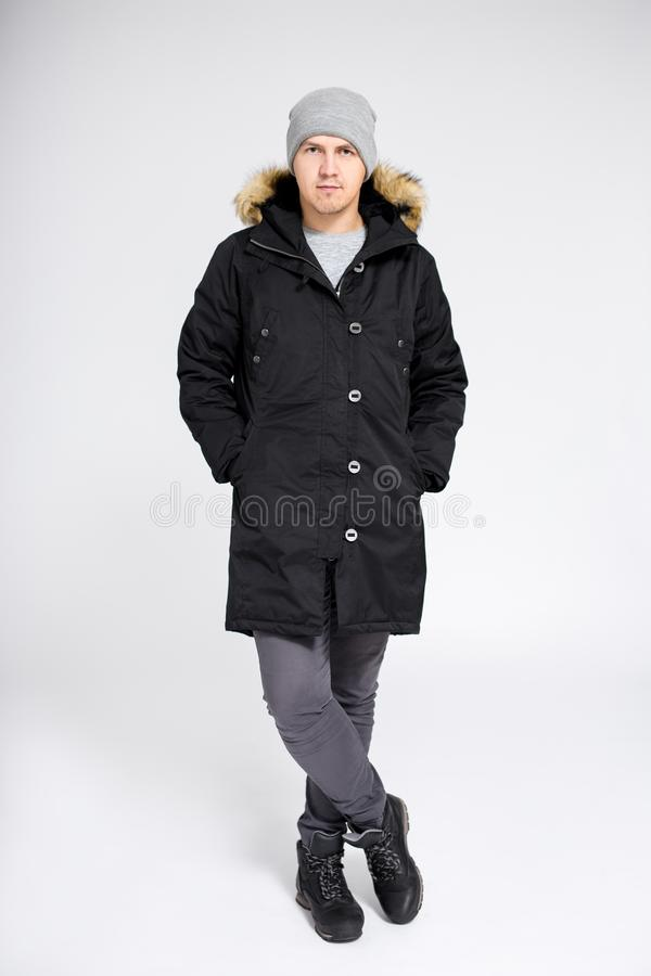 Fell length portrait of young handsome man in warm winter clothes over gray background stock image
