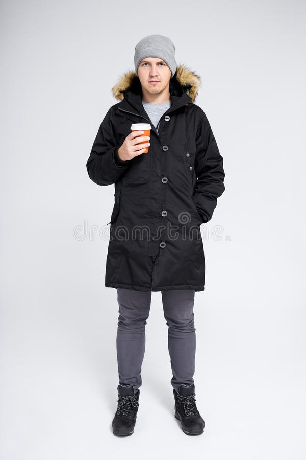Fell length portrait of young handsome man in warm winter jacket drinking coffee over gray background royalty free stock photos