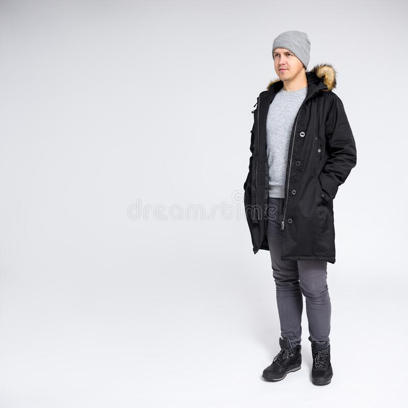 Fell length portrait of young man in warm winter clothes over gray background with copy space royalty free stock photos