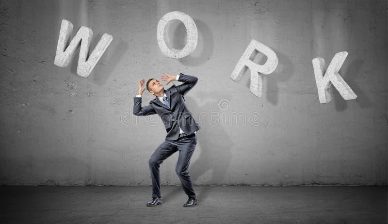 Felle eines arbeiten erschrockene Geschäftsmannes unter den großen konkreten Buchstaben, die ein Wort machen, über ihm auf einem  lizenzfreie stockbilder