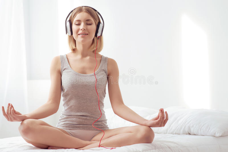 Felling peace and wellness. Morning yoga. Young healthy smiling woman is meditating in the morning while listening to calm music royalty free stock image