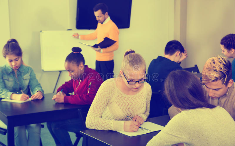 Fellow students having group work tasks during school day. Diligent serious fellow students having group work tasks during school day stock images