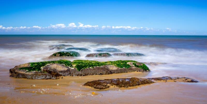 Felsen auf der langen Belichtung des Strandes lizenzfreie stockfotos