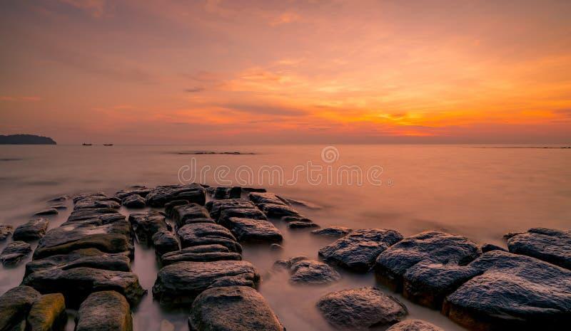 Felsen auf Steinstrand bei Sonnenuntergang Schöner Strandsonnenunterganghimmel Dämmerungsmeer und -himmel Tropisches Meer an der  stockbilder