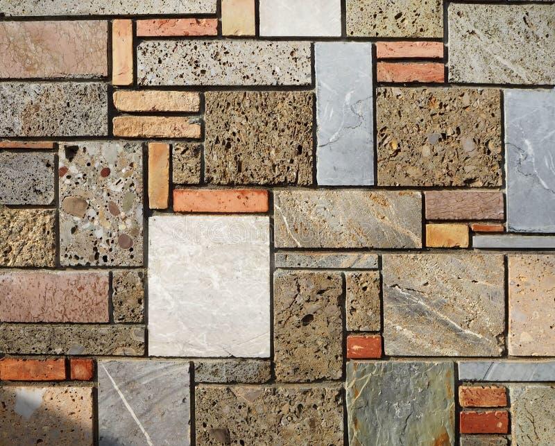 Felsen mit Moos Wand mit Ziegelsteinen und Blöcken von Poliersteinen von verschiedenen Farben und von Größen, geometrisch arrange lizenzfreie stockfotografie