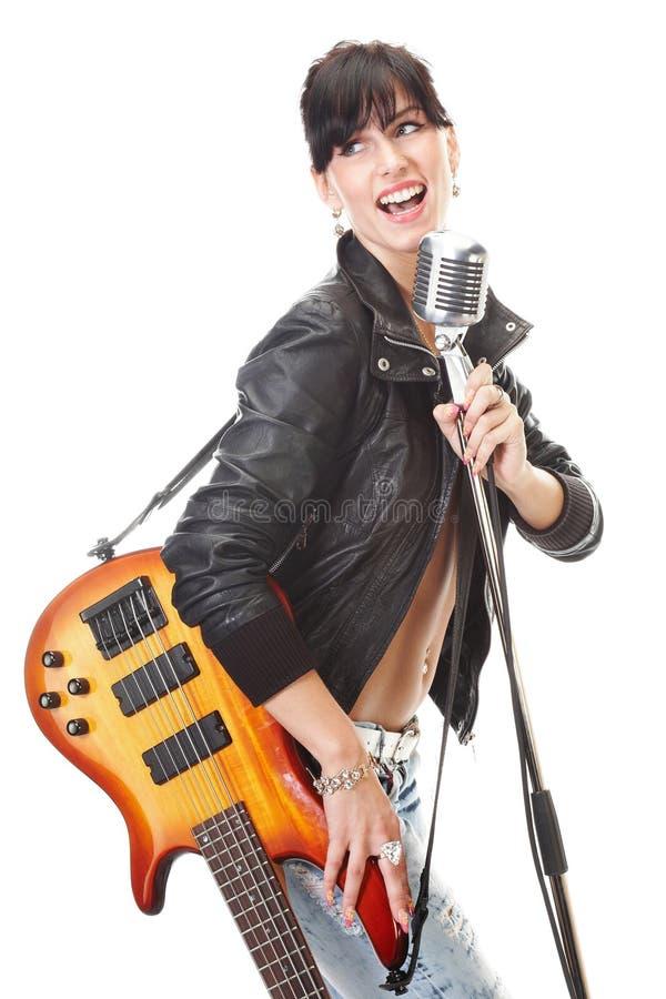 Felsen-N-rollen Sie das Mädchen, das eine Gitarre anhält, die in singt, rösten stockfotografie