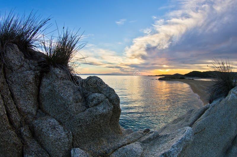 Felsen, Sand, Meer und ein Strand mit einer kleinen Höhle bei Sonnenuntergang, Sithonia stockfotografie