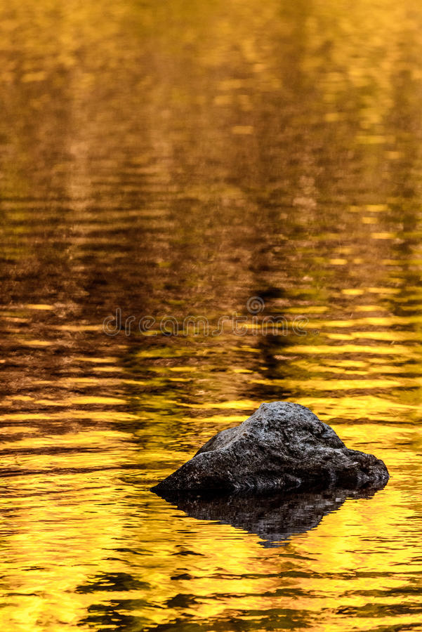 Felsen- und Goldherbstseereflexionen stockbild
