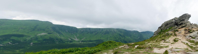 Felsen und grüne Berglandschaft stockfotografie