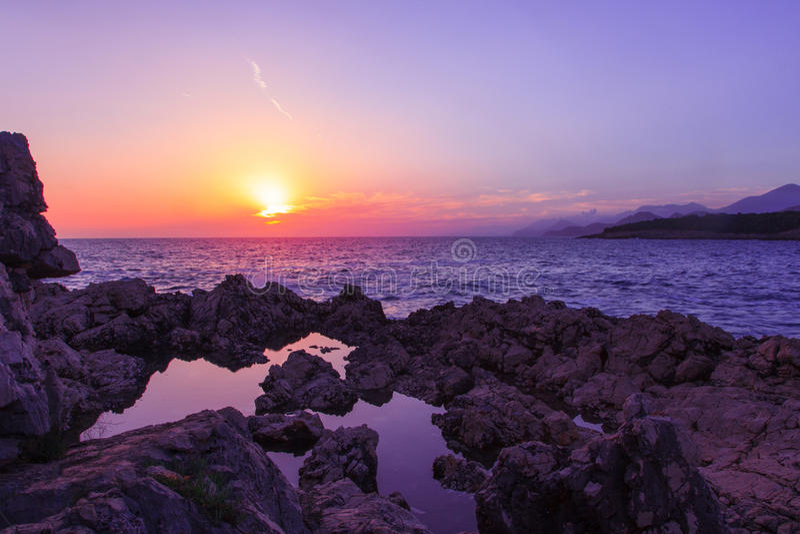 Felsen und ihre Reflexion im Meer bei Sonnenaufgang lizenzfreies stockbild