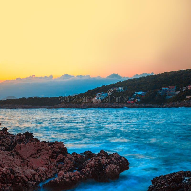 Felsen und ihre Reflexion im Meer bei Sonnenaufgang lizenzfreie stockfotografie