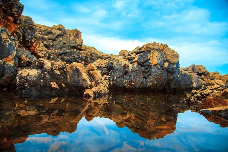 Felsen und ihre Reflexion im Meer tagsüber stockfoto