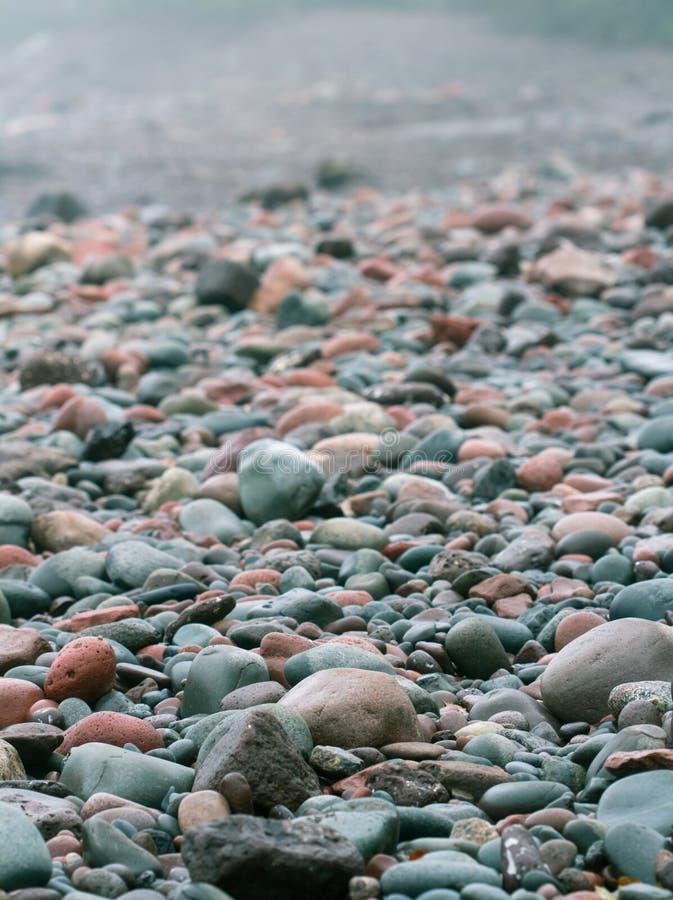 Felsen und Kiesel auf einem Strand stockfotos