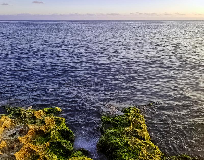 Felsen vor Malecon und Atlantik während des Sonnenuntergangs - Havana, Kuba stockfotografie
