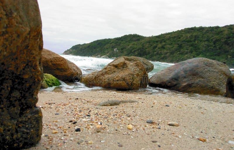 Felsen, Welle, Sand und mountai auf dem Strand stockbilder