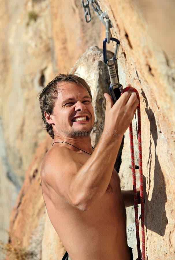 Felsenbergsteiger, der kämpft, um Seil am Schnelldr. zu befestigen stockfotos