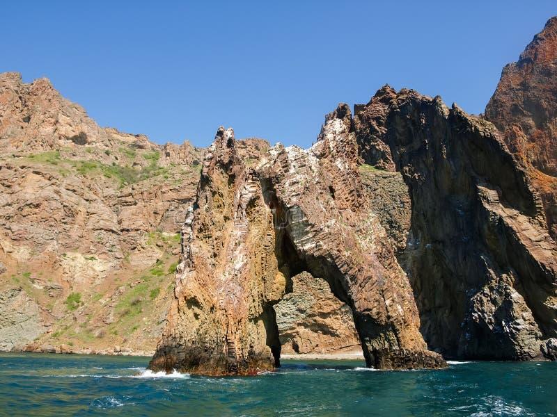 Felsenbogen des vulkanischen Ursprung nahe dem Seeufer lizenzfreies stockbild