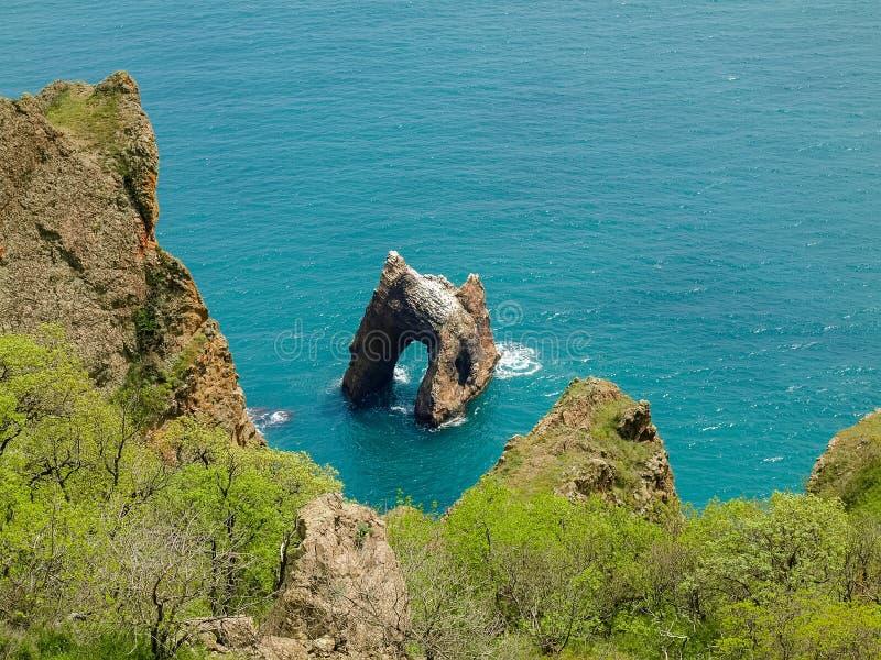 Felsenbogen des vulkanischen Ursprung nahe dem Seeufer lizenzfreie stockbilder