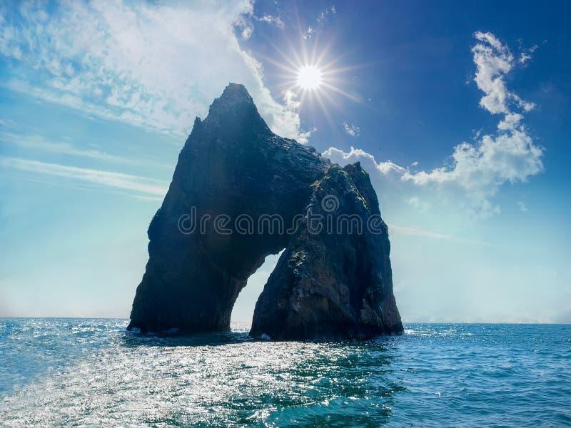 Felsenbogen des vulkanischen Ursprung nahe dem Seeufer stockfotos