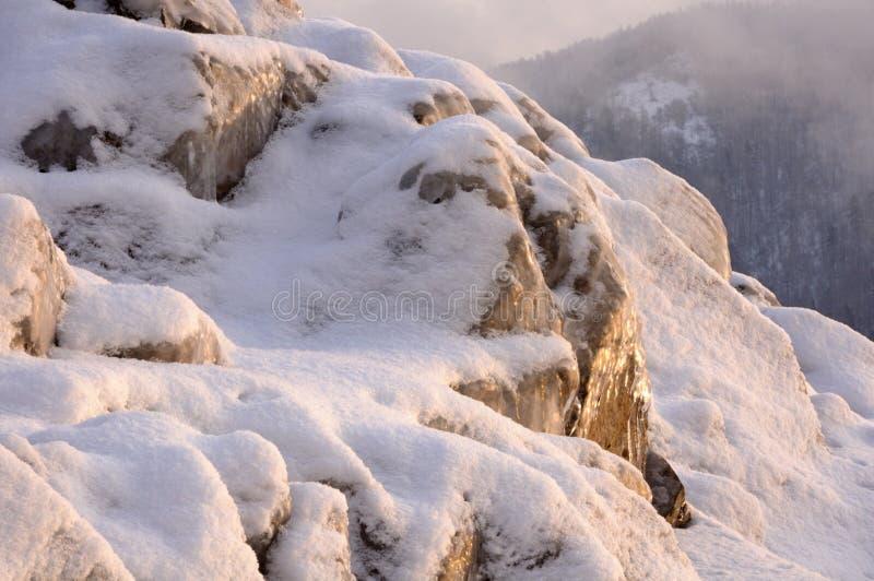 Felsensteine bedeckt mit Eis, Schnee und Eiszapfen auf der der Jenissei-Bank während der nebeligen Dämmerung des Winters lizenzfreie stockfotografie