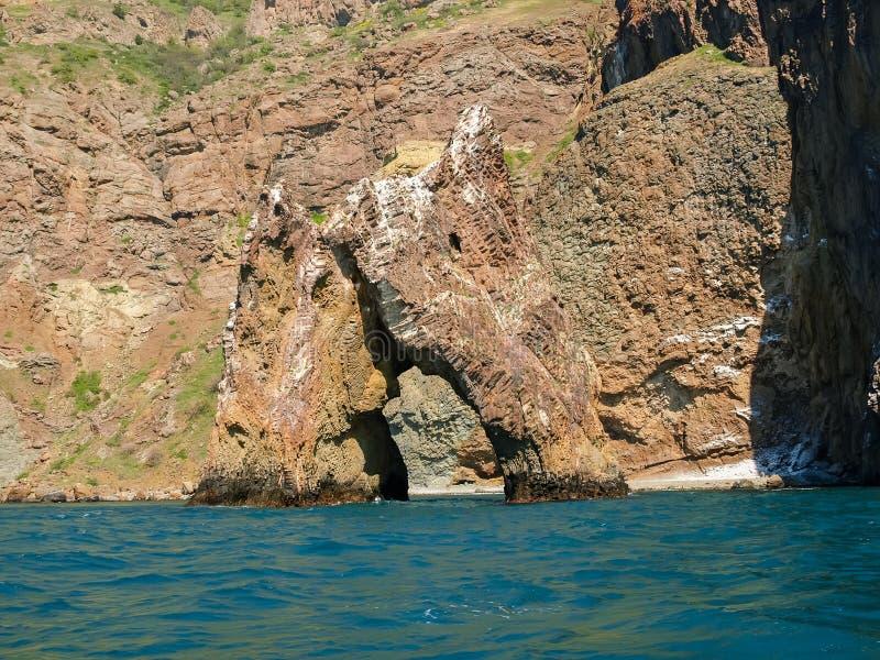 Felsentor des vulkanischen Ursprung gegen das Seeufer lizenzfreies stockfoto