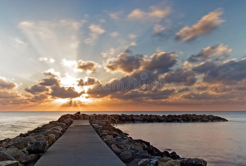 Felsige Anlegestelle/Pier bei Sonnenaufgang mit drastischem bewölkter Himmel und des ruhigen Sees, Cala bona, Mallorca, Spanien lizenzfreie stockfotografie