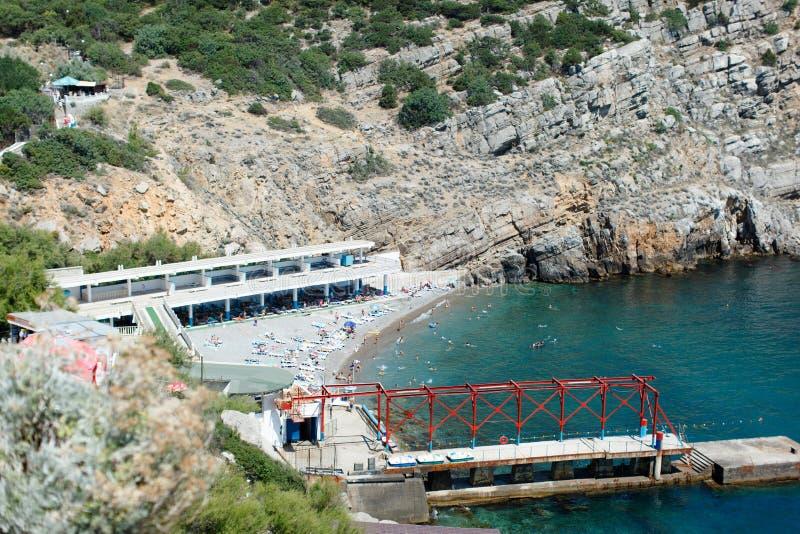 Felsige Küste des Schwarzen Meers, in der Bucht nehmen ein Sonnenbad und schwimmen stillstehende Leute stockbild